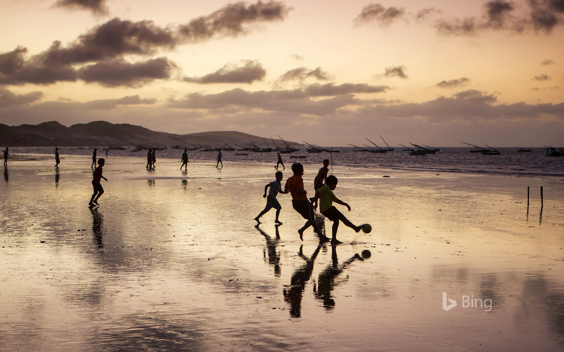 Young boys playing soccer on a beach in Ceará state, Brazil