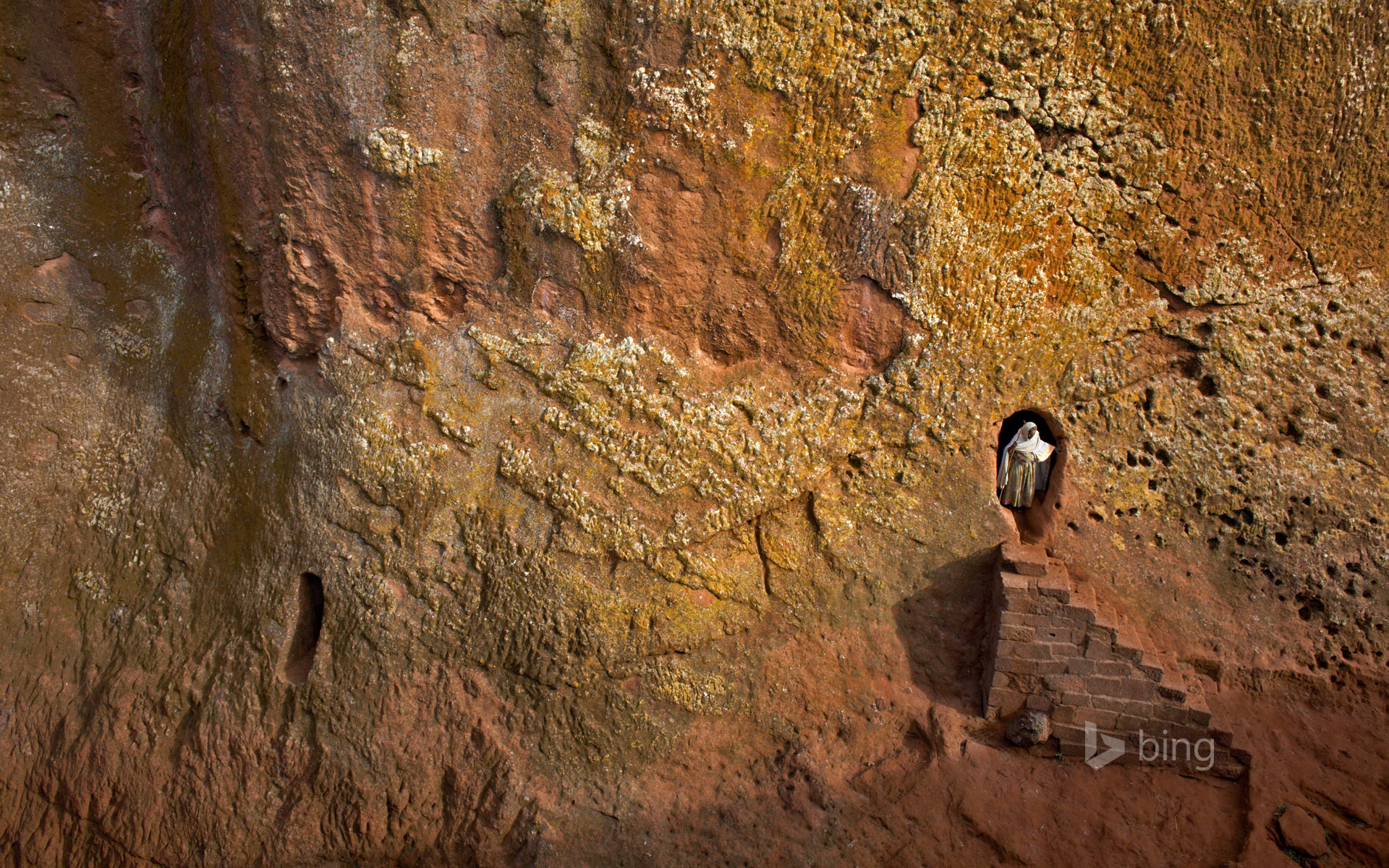 Woman emerges from a tunnel leading to Bet Amanuel, in Lalibela, Ethiopia