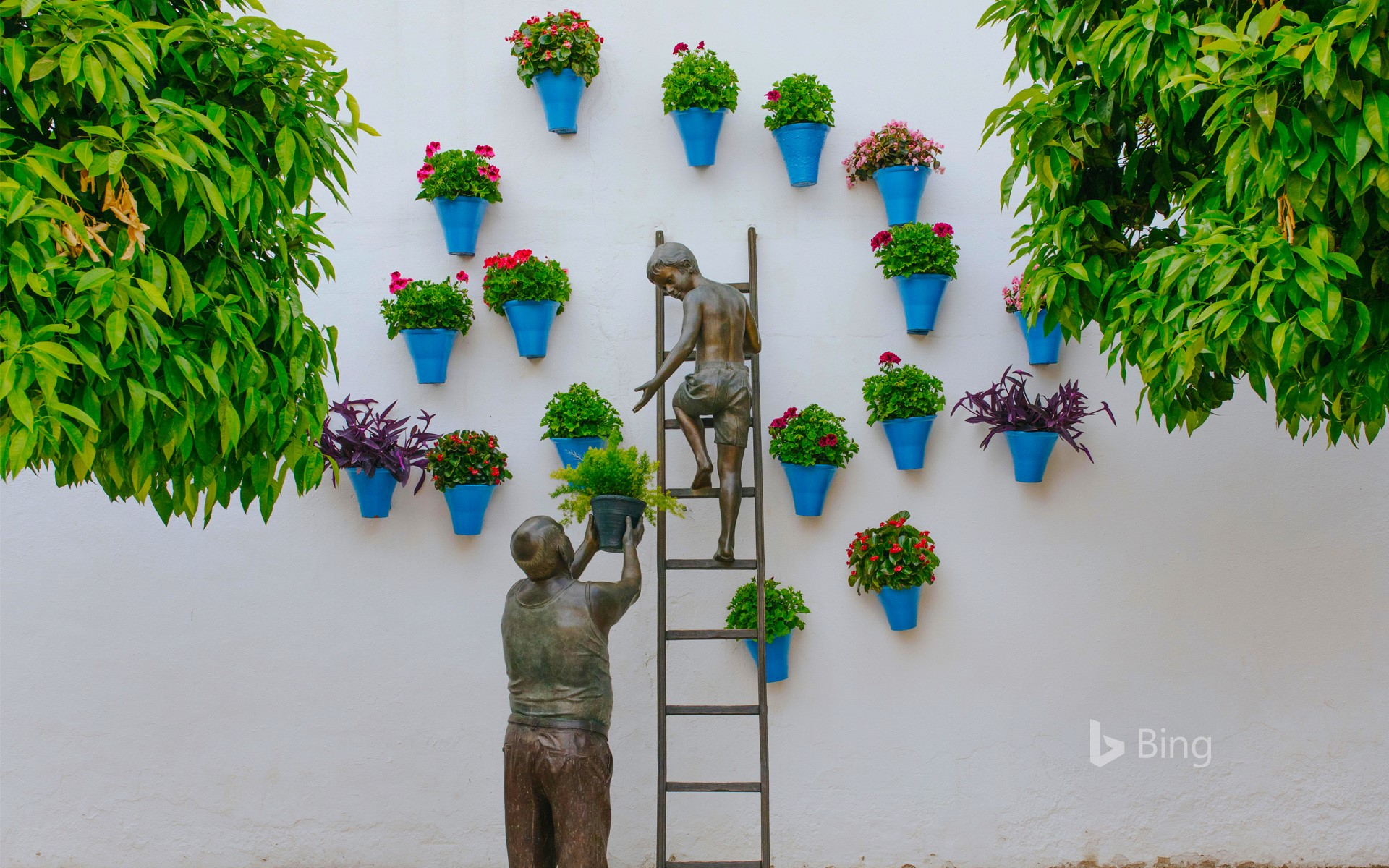Bronze sculpture of a child and his grandfather caring for plants and flowers in the San Basilio neighborhood of Córdoba, Spain