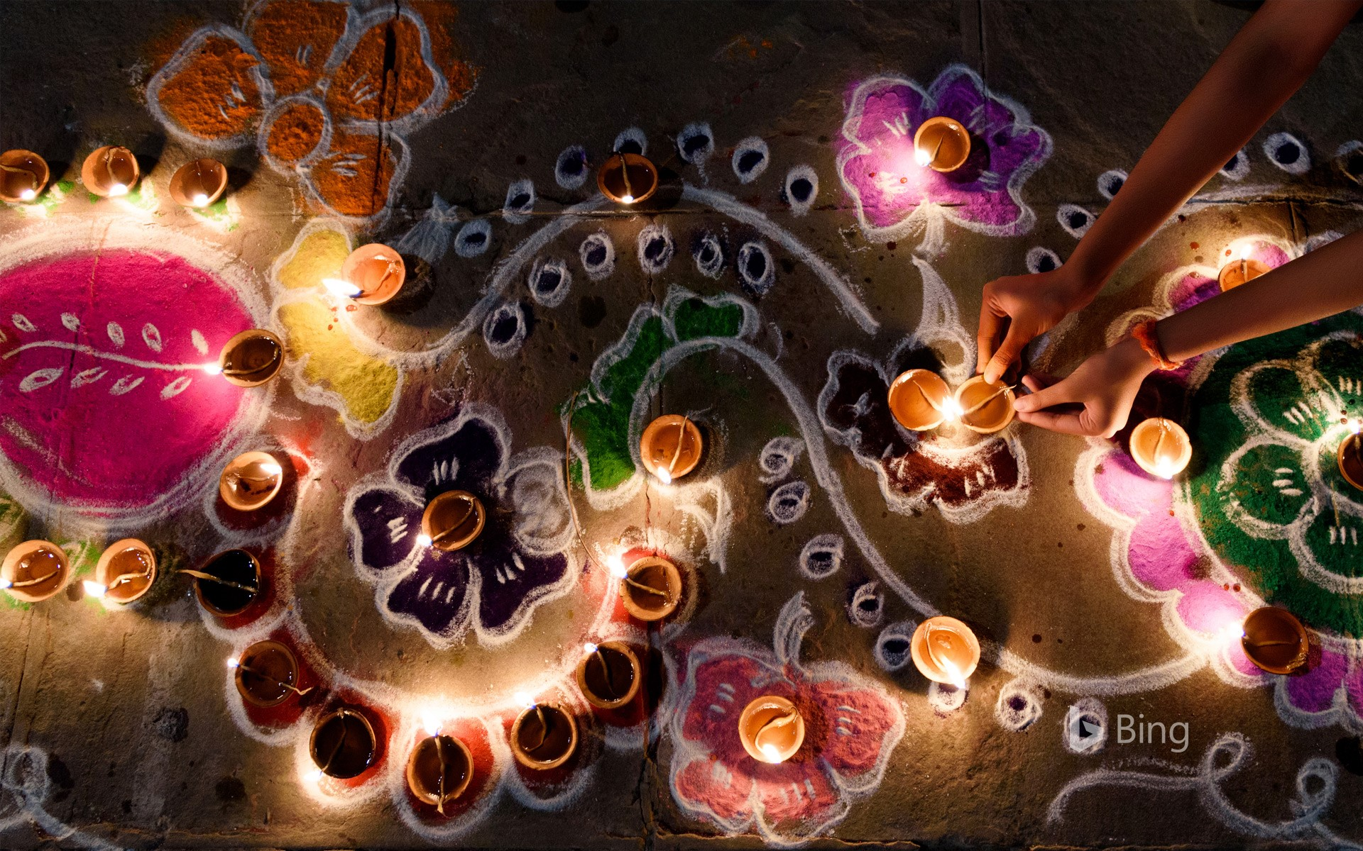 Oil lamps being arranged on rangoli during Diwali