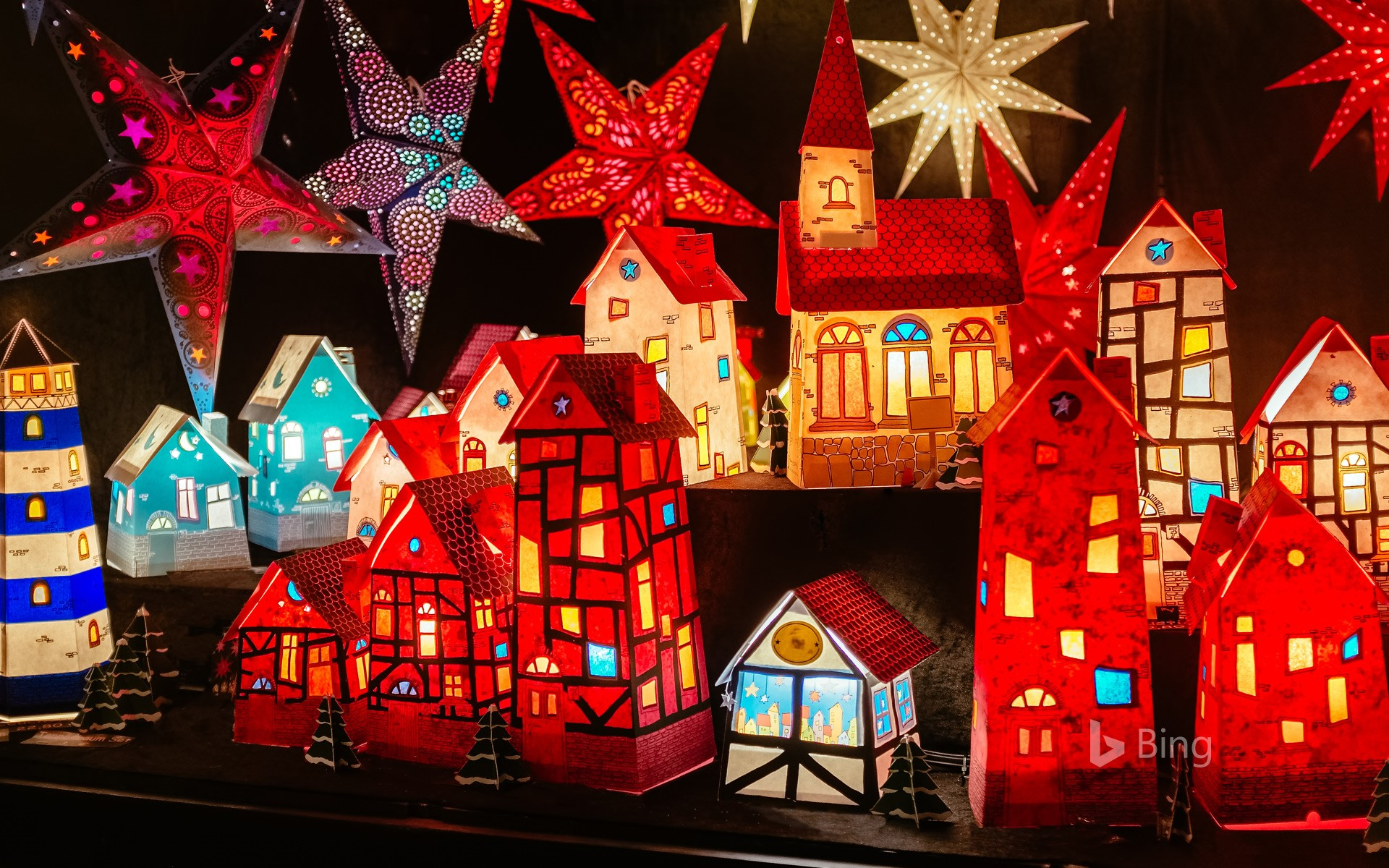 Luminous paper houses and poinsettias at a Christmas market in Hanover, Lower Saxony
