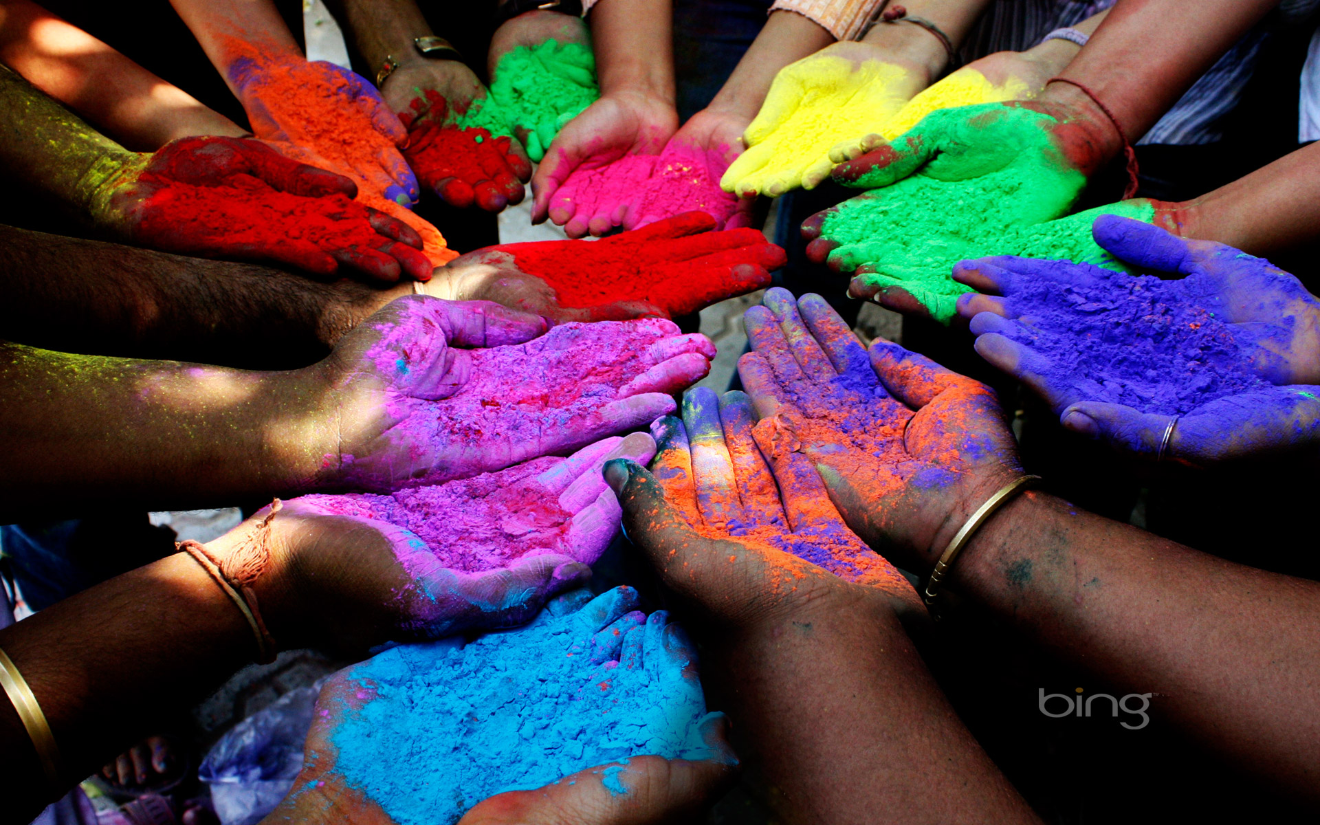 People holding colored powders to celebrate Holi (Festival of Colors) in Ahmedabad, India
