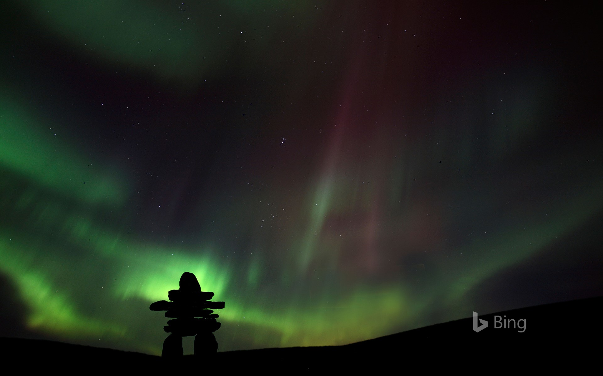 Inukshuk silhouetted against the northern lights in Barren Lands, Northwest Territories, Canada