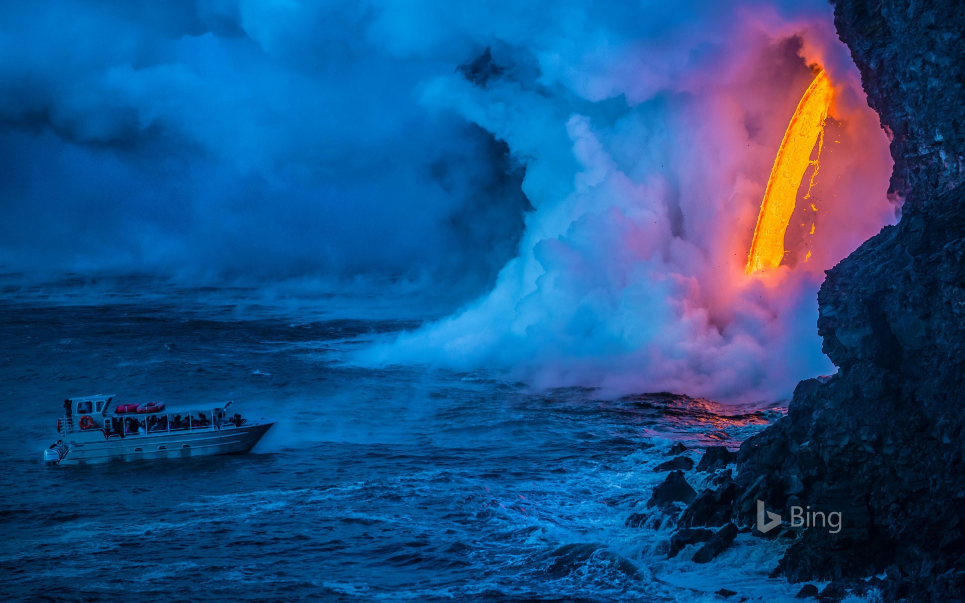 A lava flow hits water to create an explosion as a tourist boat passes, Hawaii Volcanoes National Park, USA