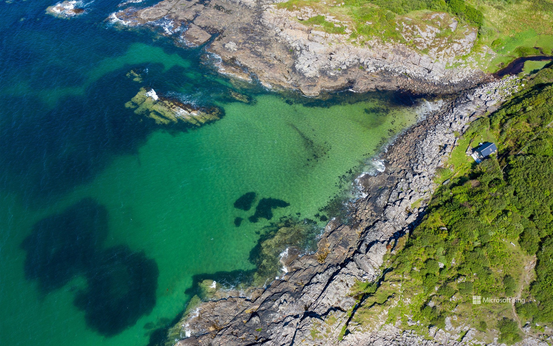 Aerial shot of waves lapping up onto rocks in Portuairk Bay, Ardnamurchan, Lochaber