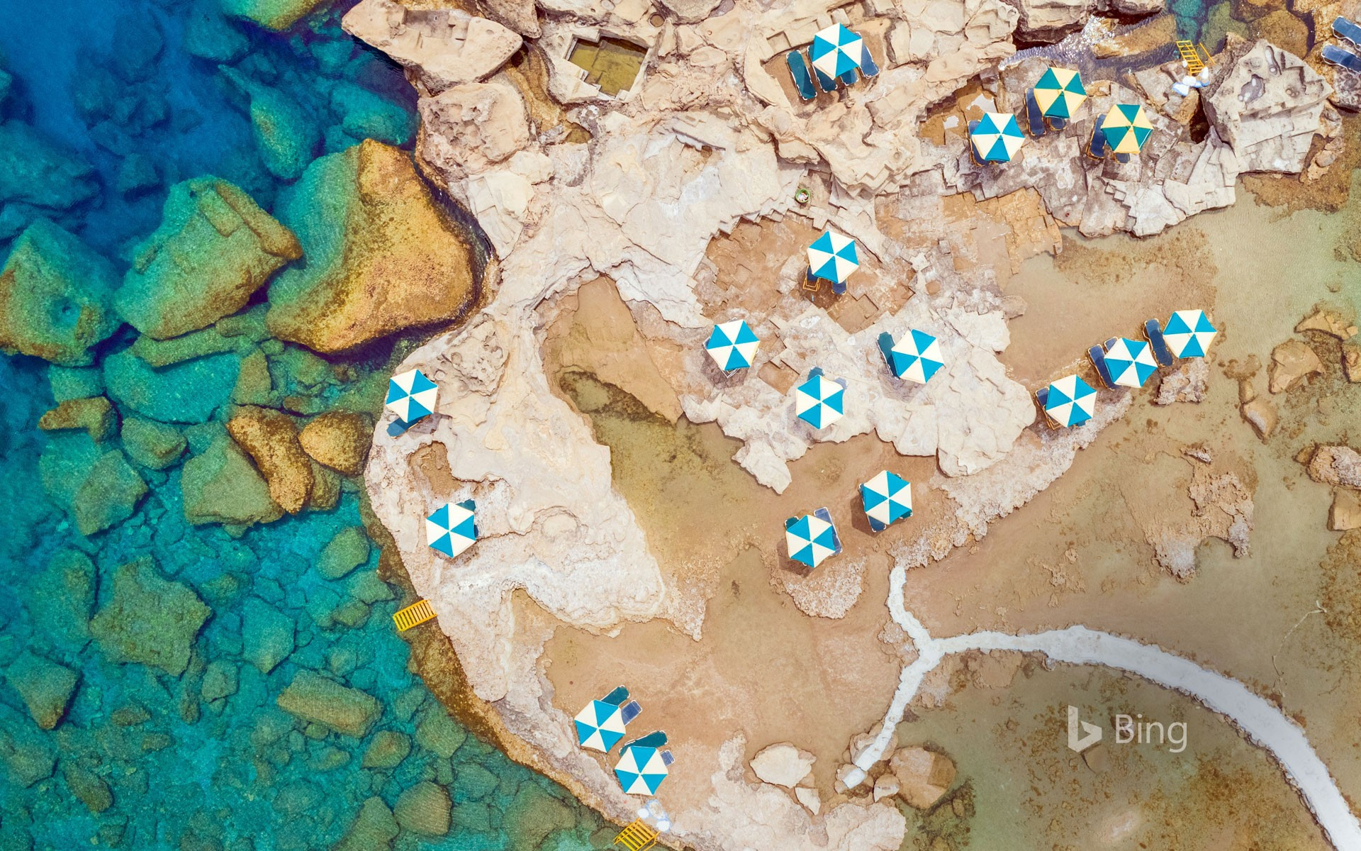 Aerial view of blue and white parasols on the rocky coast of Rhodes, an island in Greece