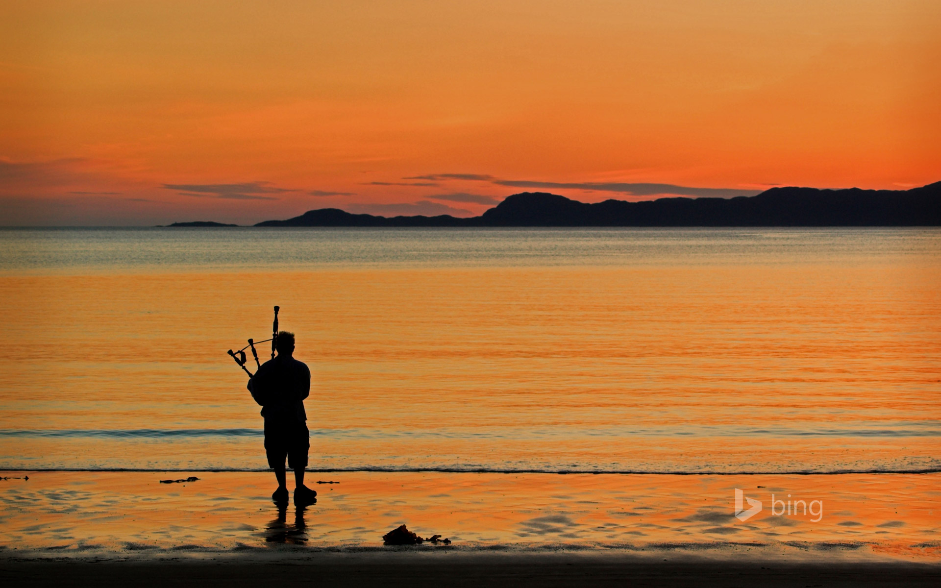 A bagpiper on Arisaig beach in Scotland
