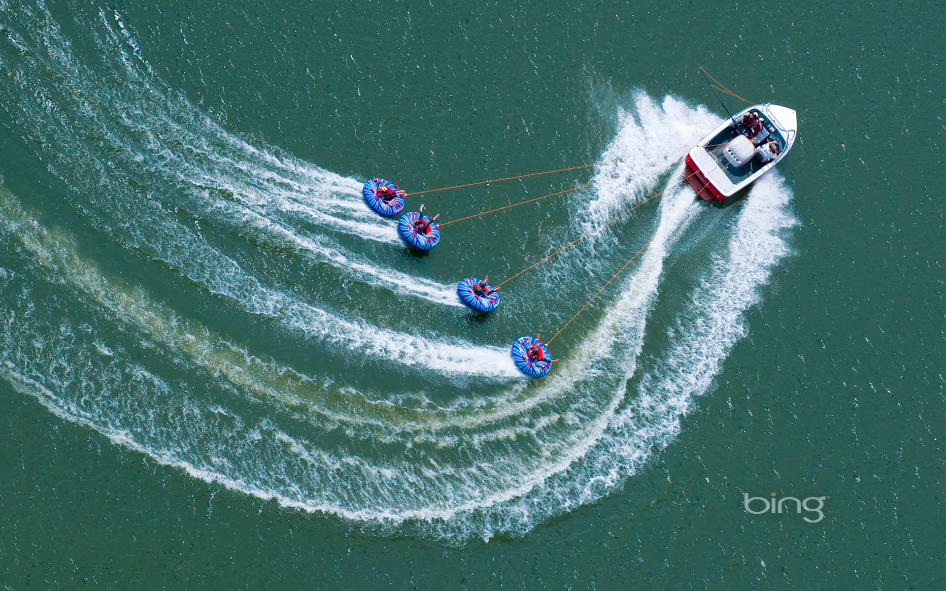 "A speedboat tows ""tubers"" on Abbey Lake in Surrey, England"