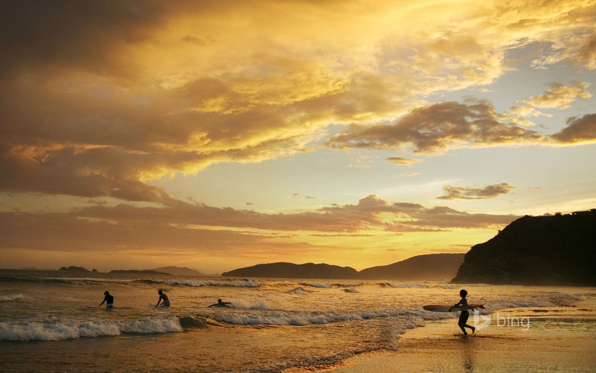 People surfing at dusk, Geriba Beach, Buzios, Brazil