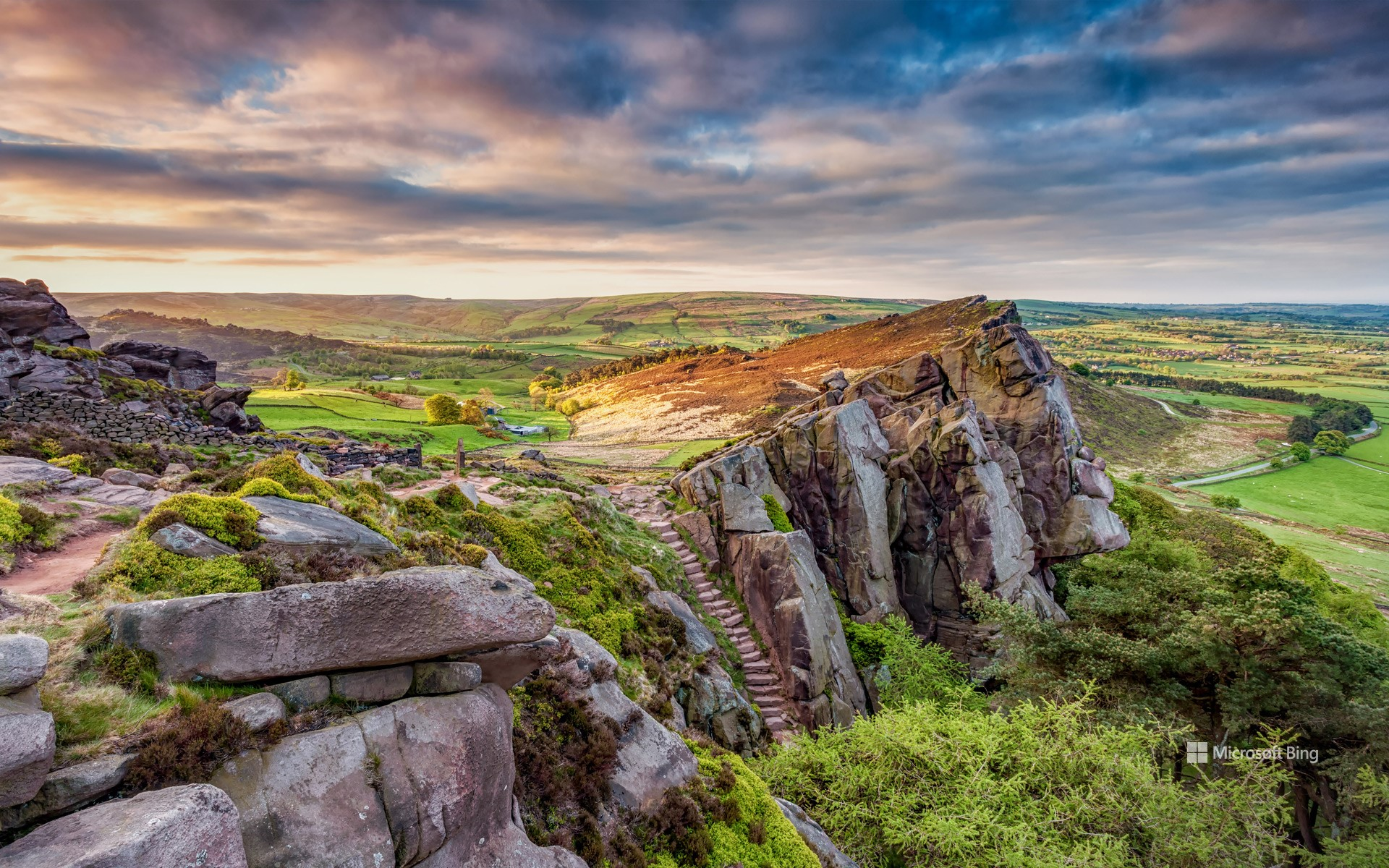 View of the rocky gritstone edge of The Roaches looking over the patchwork landscape, Peak District, Staffordshire.