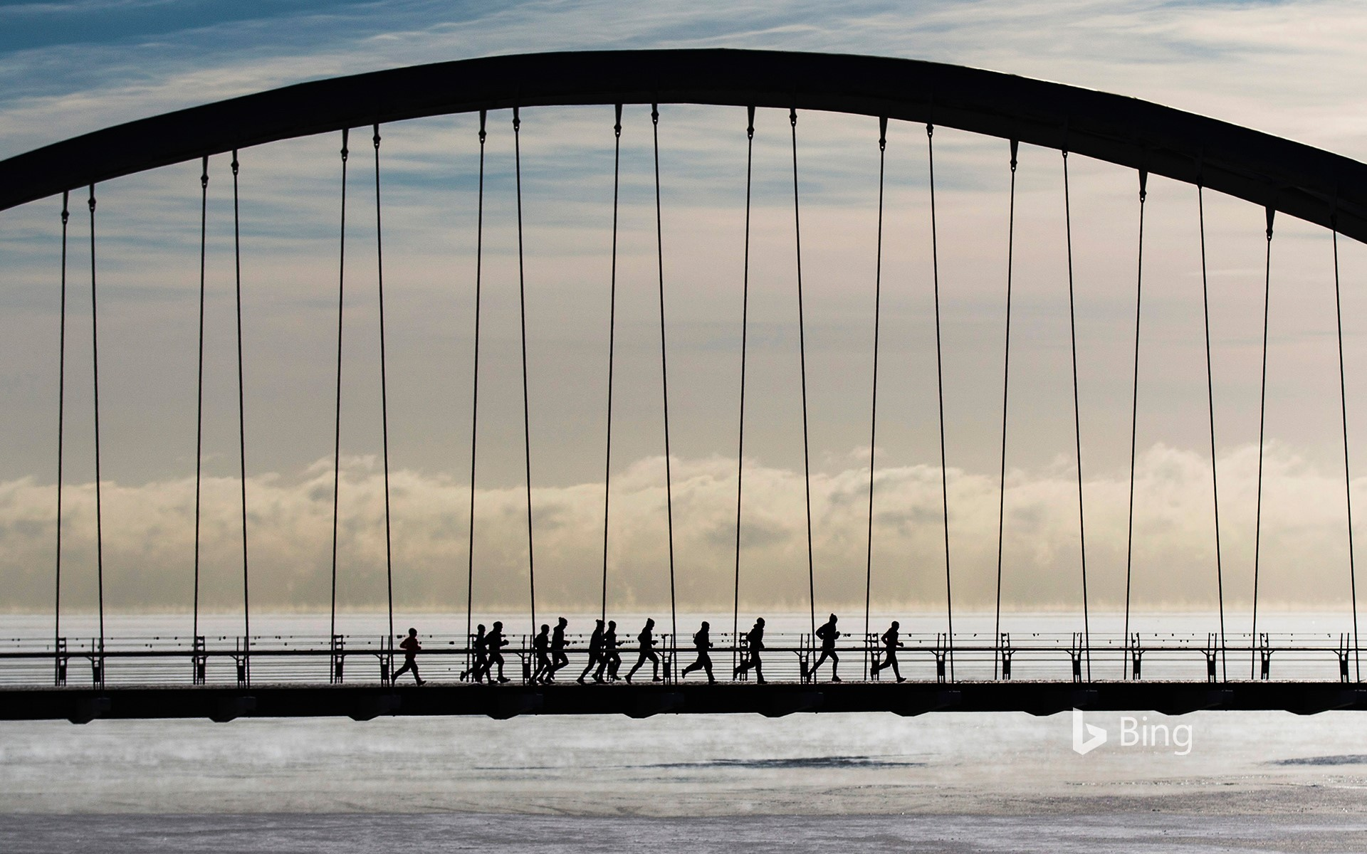 A group of joggers run across the Humber Bay Arch Bridge in Toronto, Canada