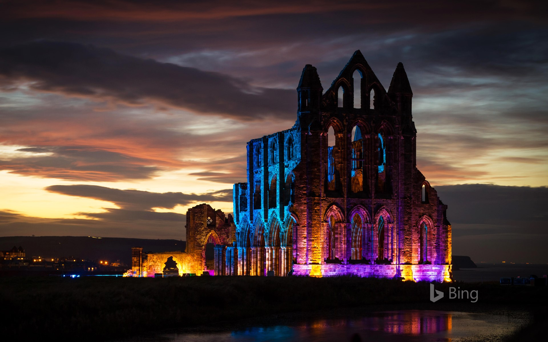 Whitby Abbey illuminated with coloured floodlights in North Yorkshire