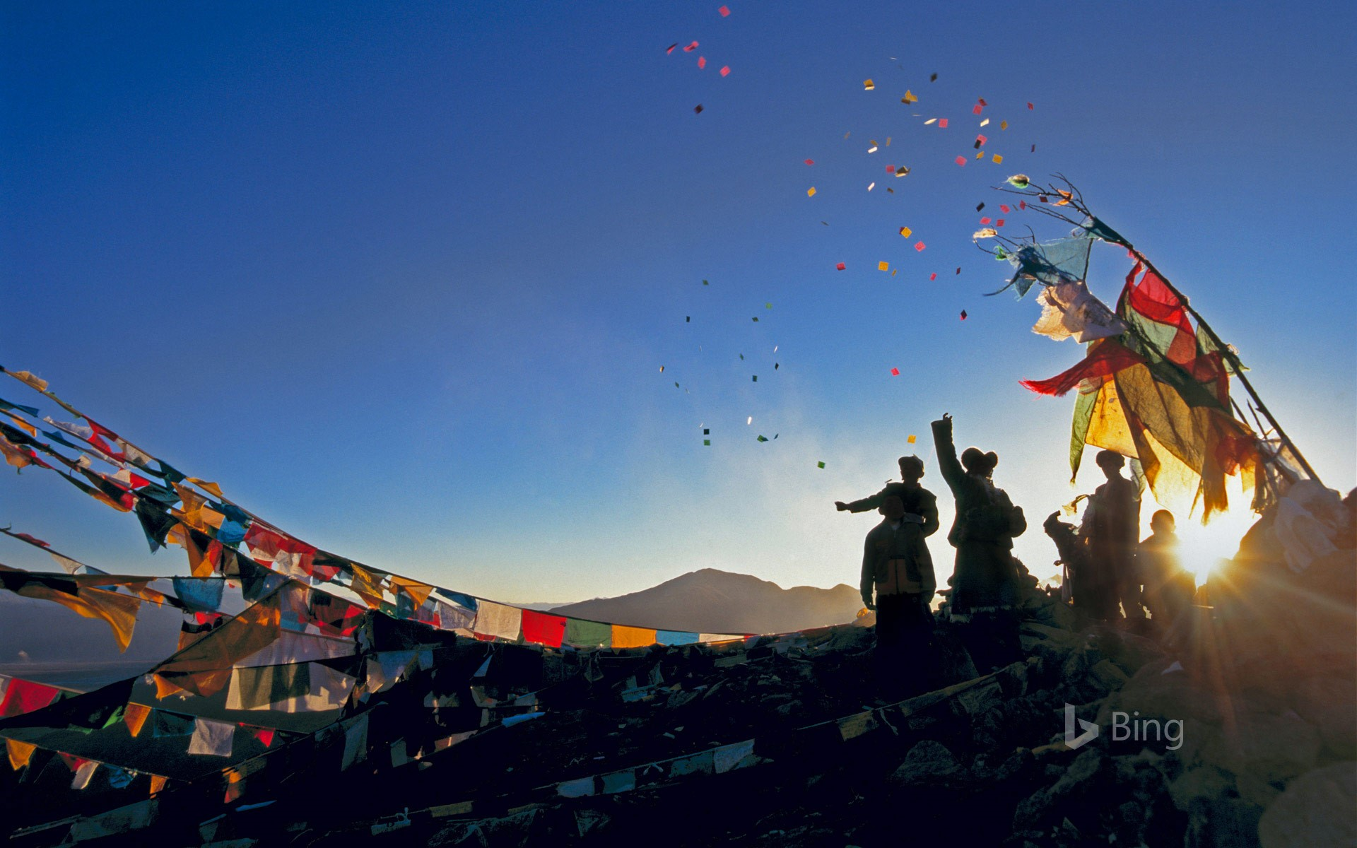Pilgrims throwing wind horses into the air above Ganden Monastery for the New Year in Tibet, China
